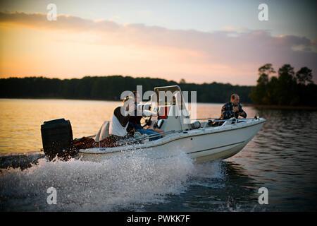 Photographers taking photographs from speeding boat - Stock Photo
