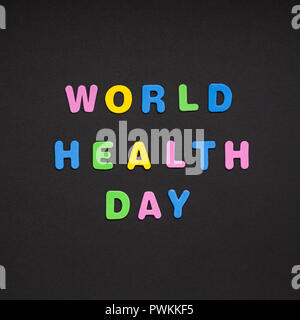 Creative colorful text made from plastic letters World Health Day writing on black paper background with copy space. Holiday message concept, celebrat - Stock Photo