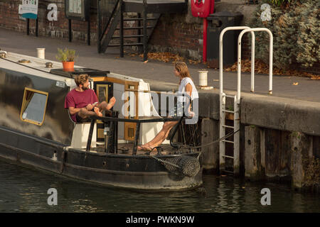 Young people on a river boat, in the redeveloped calm oasis  Lime House Basin, London, UK, connecting the River Thames with canals in and out the city - Stock Photo