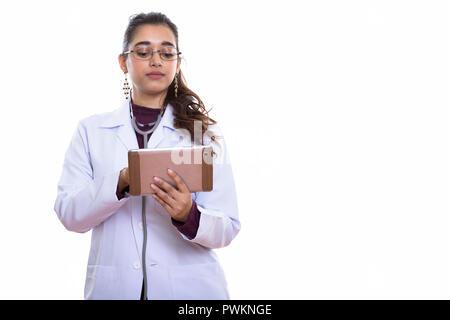 Studio shot of young beautiful Indian woman doctor using digital - Stock Photo