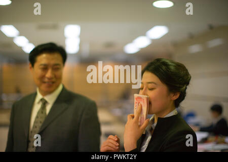 Businesswoman closing her eyes while standing next to her colleague and sniffing a stack of dollar bills. - Stock Photo