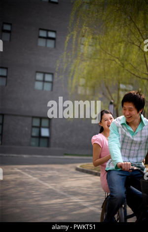 Young adult couple riding a bicycle along a park. - Stock Photo