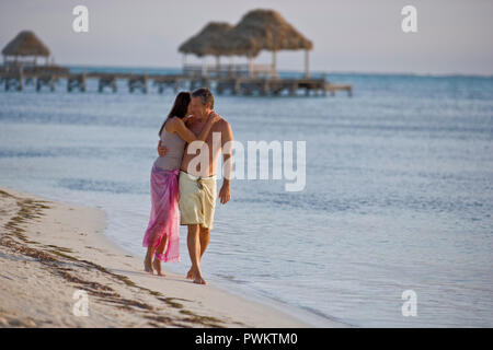 Couple walking along the beach - Stock Photo