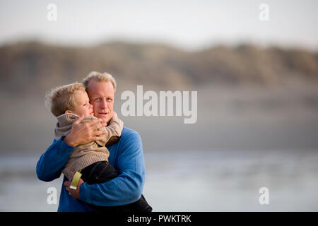 Portrait of a mature man hugging his young grandson on a remote beach Stock Photo