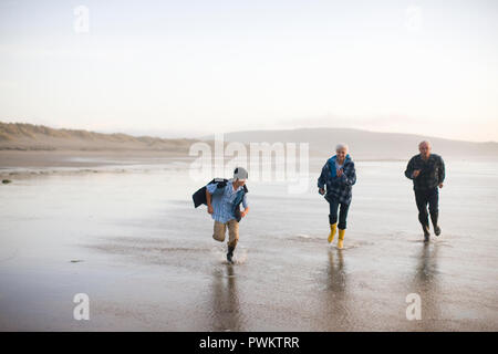 Smiling boy running along a remote beach with his grandparents while wearing gumboots. - Stock Photo