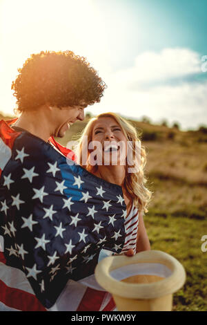 Happy young couple enjoys a sunny day in nature. They're hugging each other, wrapped in american flag. - Stock Photo