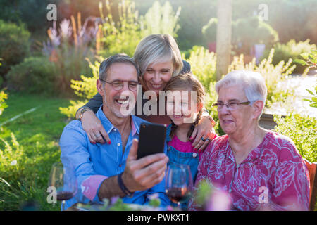 In the summer, a family of three generations having fun around a table in the garden sharing a meal. They are doing a selfie for memories - Stock Photo