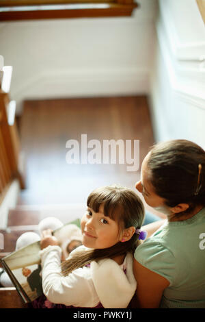 Woman and her young daughter sit on a flight of stairs. - Stock Photo