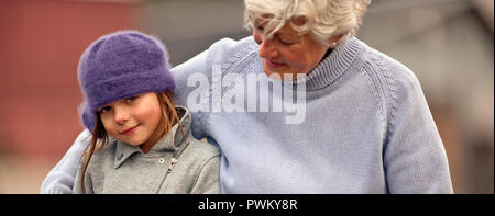 Portrait of young girl and her grandmother. - Stock Photo