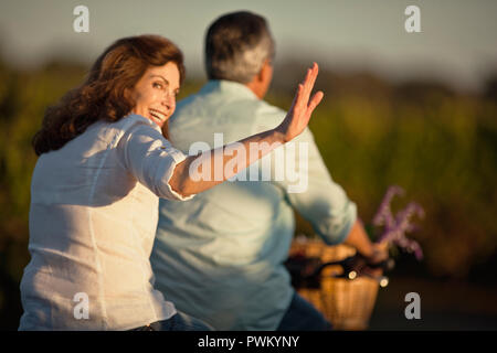 Middle-aged woman having fun riding the bicycle with her husband in the vineyard. - Stock Photo