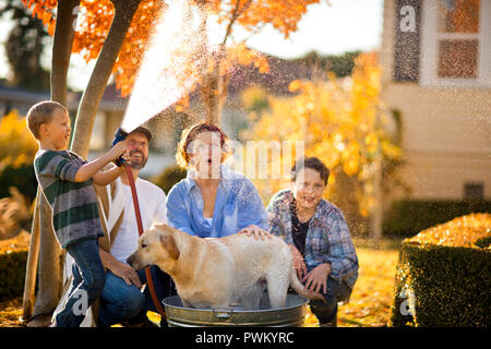 Family having fun washing their dog in a tub in the backyard. - Stock Photo