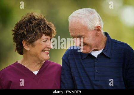 Happy mature nurse and elderly patient smiling at each other. - Stock Photo