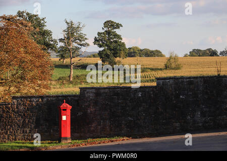 The sun shines on a bright red British post box standing in front of a dark stone wall, with planted fields and English countryside in background. - Stock Photo