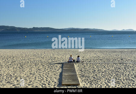Two women on the beach in a boardwalk. Golden sand, clear water and blue sky. Sunny day. Galicia, Spain. - Stock Photo