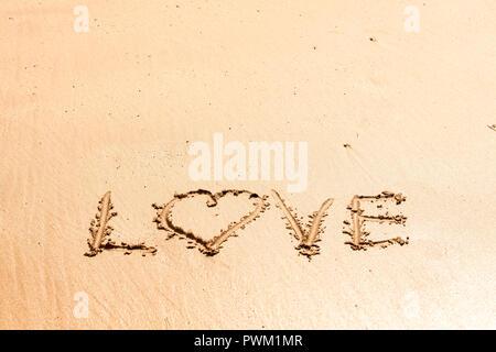 Word 'love' written on the wet sea sand - Stock Photo