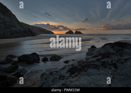 Sunset over Holywell Beach overlooking Carters Rocks on the North Cornish Coast of Cornwall - Stock Photo