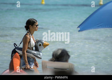 A young brunette woman in a bra and shorts walks on the beach carrying an inflatable duck for swimming. Beach of Santa Giulia in Corsica. Kaczka - Stock Photo