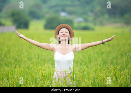 Woman traveler with backpack  hat and looking at lies on a meadow in the mountains. - Stock Photo