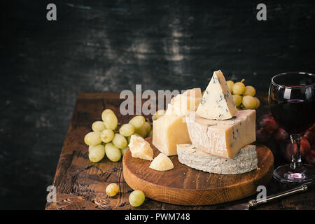 Various types of cheese and red wine still life on wooden table - Stock Photo