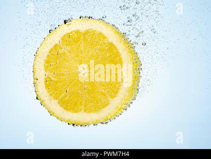 A lemon slice in water with air bubbles - Stock Photo