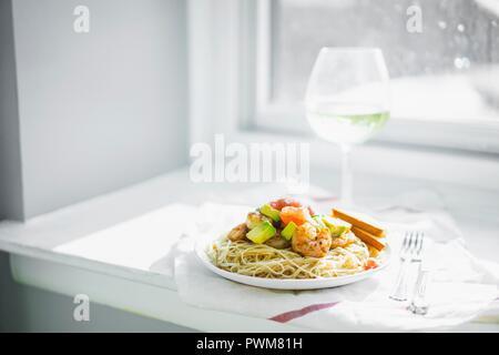 Spaghetti with prawns and avocado - Stock Photo