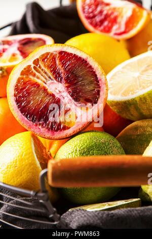 Various citrus fruit in a wire basket - Stock Photo