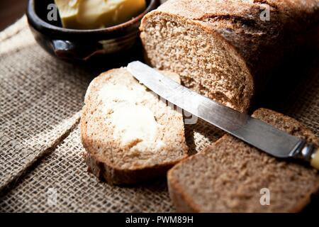 Freshly baked wholemeal bread with salted butter - Stock Photo