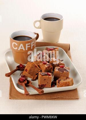 Chocolate brownies with dried cranberries served with coffee - Stock Photo