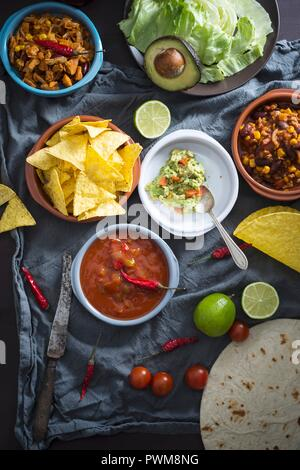 Vegan Mexican dishes: guacamole with tortilla chips, salsa, pulled jackfruit, chili sin carne - Stock Photo