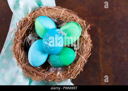 Dyed Easter eggs with batik patterns in a basket - Stock Photo