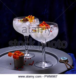 Gin tonic with ice cubes and flowers in two glasses - Stock Photo