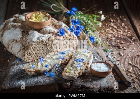 Homemade wholemeal bread with butter and salt on an old wooden board - Stock Photo