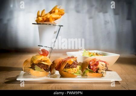 Three mini burgers on a serving platter with a cone of chips in the background - Stock Photo