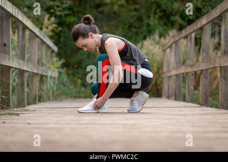 sporty woman tying up her trainers before exercise and running - Stock Photo