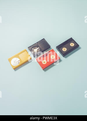 Four VHS tapes, one yellow, one red, two blacks, arranged meticulously to form zig-zag pattern - Stock Photo