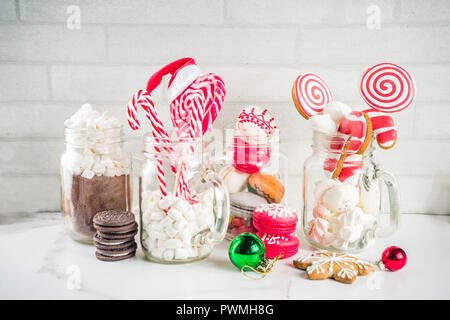Set of various christmas sweets, gingerbread, cookies, macarons, marshmallow with hot chocolate ingredients, in mason jar glasses, white background co - Stock Photo
