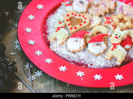 Royal icing decorated christmas cookies on red festive plate with snowflakes - Stock Photo