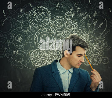 Hard thinking serious man over blackboard background gear brain arrows and mess as thoughts. Concept for mental, psychological development. - Stock Photo