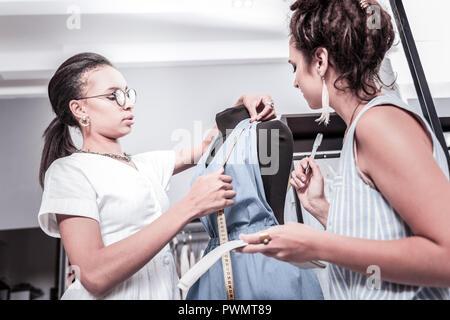 Dark-haired assistant of designer measuring shoulders of summer jumpsuit - Stock Photo