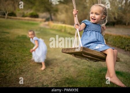 Two happy sisters playing on a swing in the garden. - Stock Photo