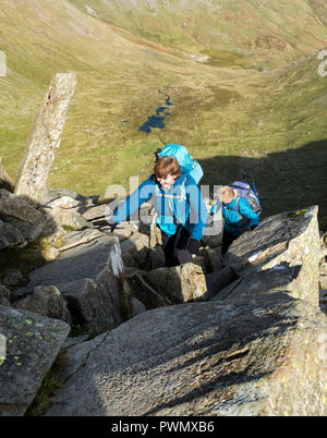 Two People Scrambling on Swirral Edge, Helvellyn, Lake District, Cumbria, UK. - Stock Photo