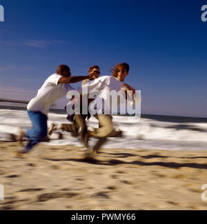 Three young men playing American football together on a sandy beach in the sunshine. - Stock Photo
