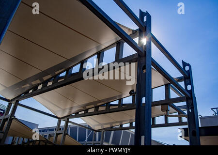Sail shade pergola made of galvanized steel and white canvas tall standing strong structure against the blue sky - Stock Photo