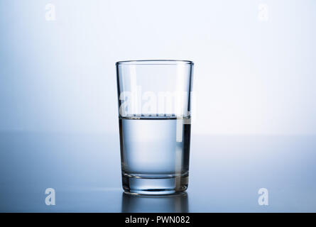 A glass of mineral water in fresh blue light. - Stock Photo