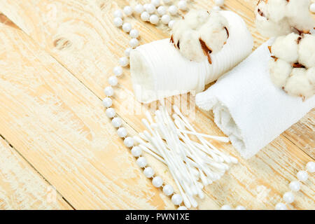 Branch of cotton plant, eared sticks, cotton pads, towel, cosmetic makeup removers tampons, hygienic sanitary swabs  on wooden background Top view. Sp - Stock Photo
