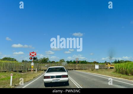 Sugarcane train crossing a road at a train crossing, Ingham, QLD, Australia - Stock Photo
