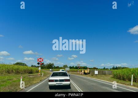 Sugarcane train crossing a road at a train crossing, Ingham, QLD, Australia - Stock Photo