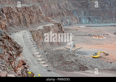 Stone crusher and excavator in a porphyry quarry. mining industry - Stock Photo