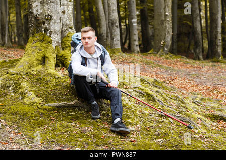 Young blonde attractive smiling man with trekking poles and camera sitting and relaxing on the moss in the forest, trekking, recreation and healthy lifestyle concept - Stock Photo
