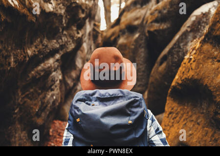 Travel young woman wearing brown hat, plaid shirt, jeans and brown boots with backpack looking on wonderful canyon with moss on rocks after hiking, travelling concept
